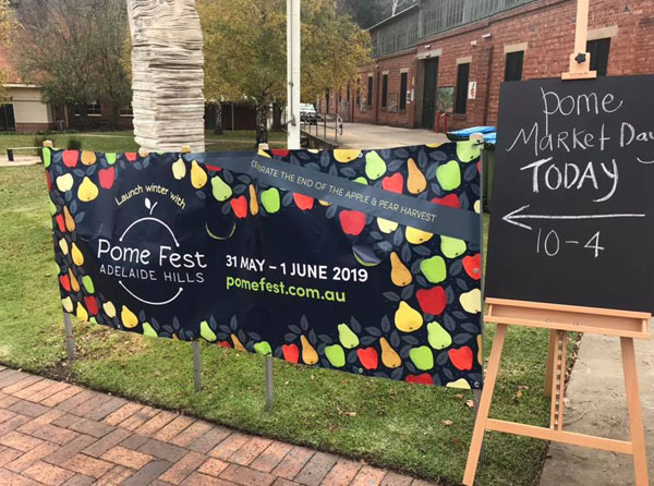 """Sign on a lawn saying """"Pome Fest Adelaide Hills 31 May - 1 June 2019"""""""