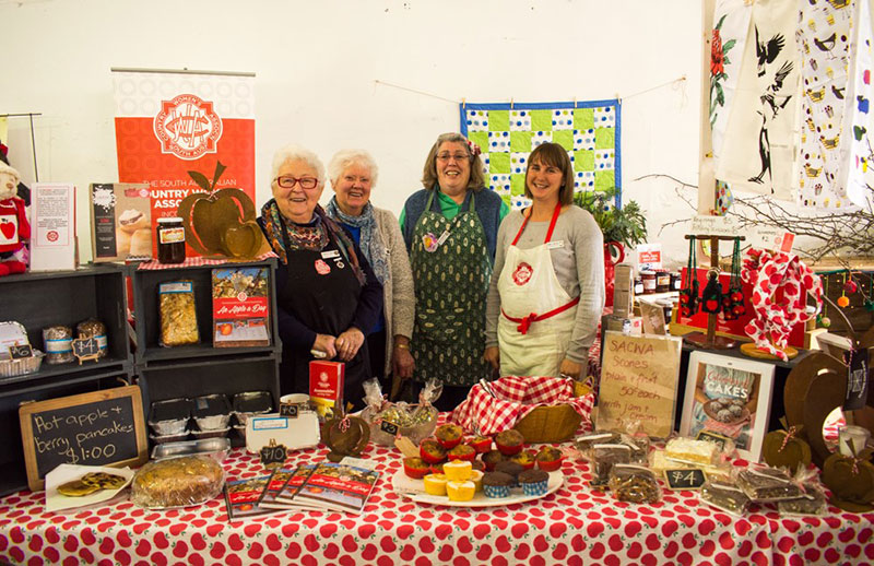 4 women behind a stall with cakes and crafts.