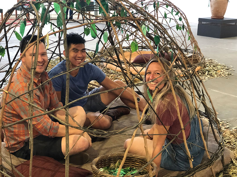 Three people sitting inside a structure.