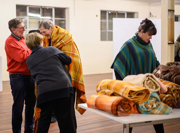 Image shows people standing near a table with blankets on it.