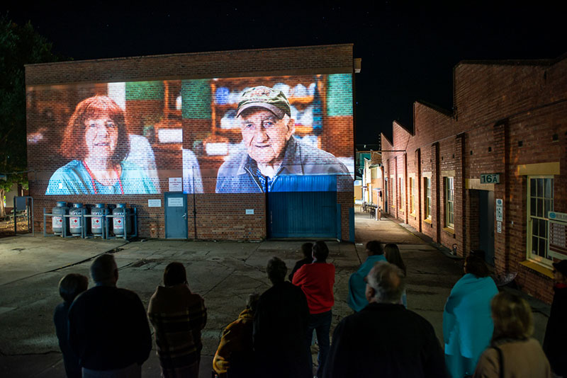 An image of two people projected onto a brick wall. A crowd is looking at it.
