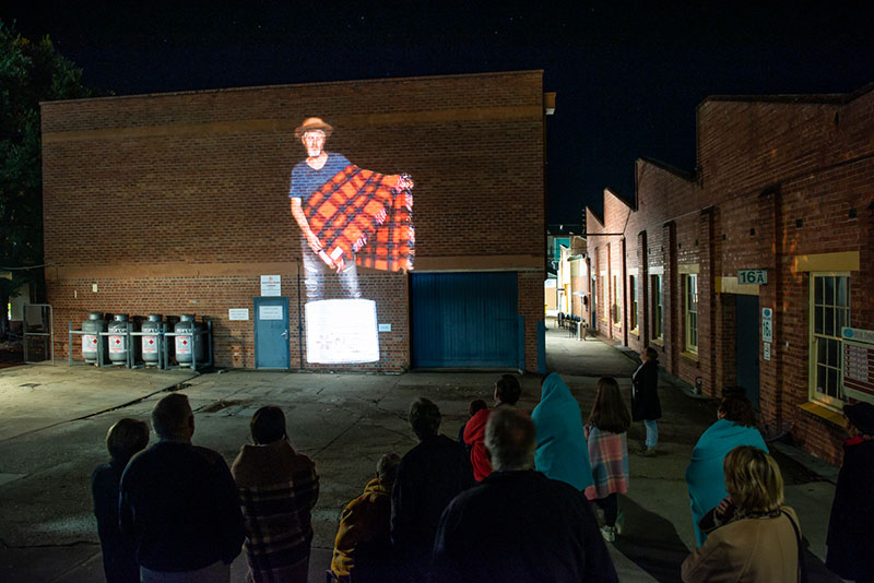 An image of a man holding a blanket is projected onto a brick wall.