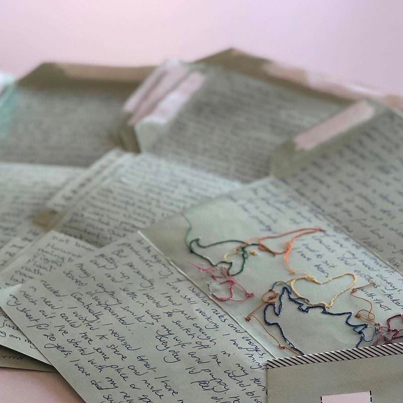 Close up of handwritten letters. One has colourful stitiching.
