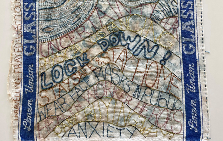 """Close up of an embroidered tea towel. The words """"uncertainty"""", """"physical distancing"""", """"lock down"""", """"stay safe stay home"""", """"wear face masks in public"""", """"healthcare heroes, """"panic buying"""" and """"anxiety"""" are stitched onto it."""