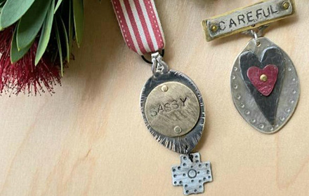 """Image shows two metal medals. One says """"Sassy"""" and one says """"Careful""""."""