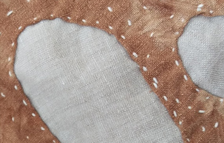 Close up of stitched material in two different colours.